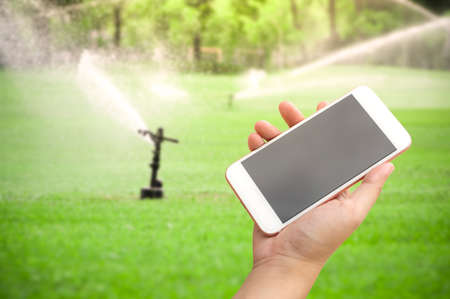 Hand holding smartphone with water sprinkler irrigation of green grass field