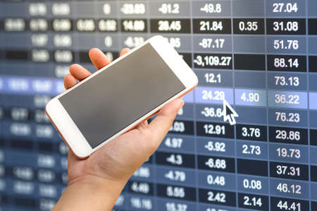 Smartphone on hand with stock market number background Stock Photo