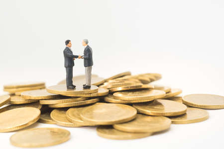 istruzione: Startup business concept. Businessman handshaking with pile of saving money coin. Archivio Fotografico