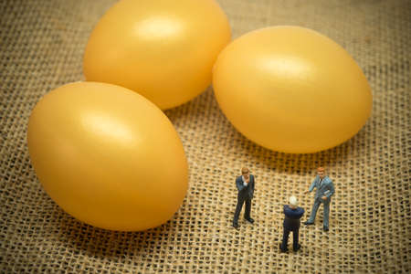 Financial investment concept. Businessmen talking in front of golden egg. Stock Photo