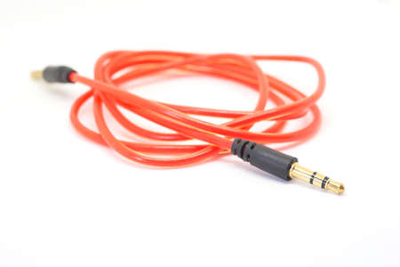 minijack: Auxiliary audio stereo cable cord male to male 3.5mm universal gold on white background