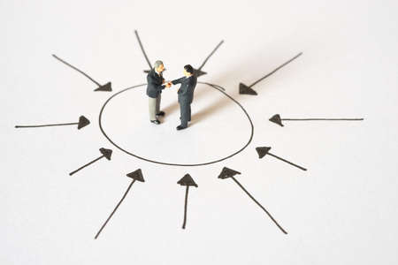 centric: Business concept of Center management. Businessmen handshaking at center of arrow point