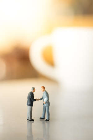 Concept of business deal. Businessmen hand shaking in cafe background.