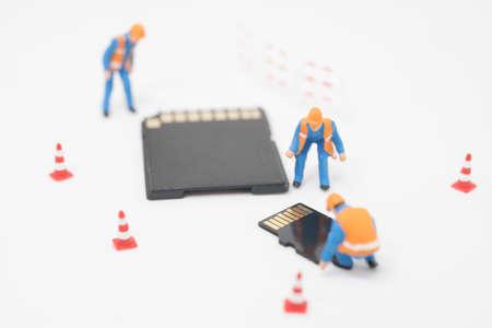 obrero trabajando: Concepto de recuperación de datos. Trabajador que trabaja en la tarjeta micro SD.