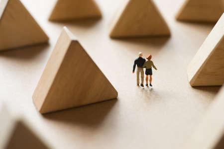 miniature: Couple life concept, Happy man and woman walking along triangle wood block scene. Stock Photo