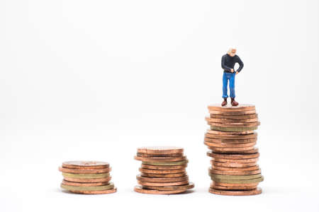 hombre pobre: Concept of poor man saving. Poor man  searching coin in pocket standing on coin stack.