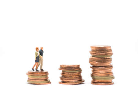 Concept of marriage money planning. Senior Couple walking over coin stack step.  스톡 콘텐츠