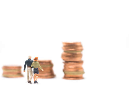 Concept of marriage money planning. Senior Couple walking to coin stack step.