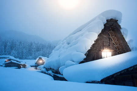 Shirakawago with heavy snowfall in winter night over moonlight