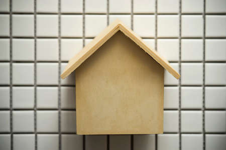 Miniature wood house on tile background