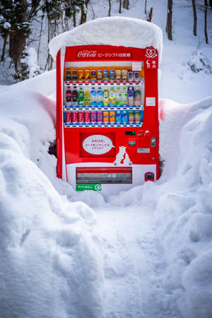 Nagano, Japan - February 13, 2017 : Coca Cola vending machine standing with heavy snow.