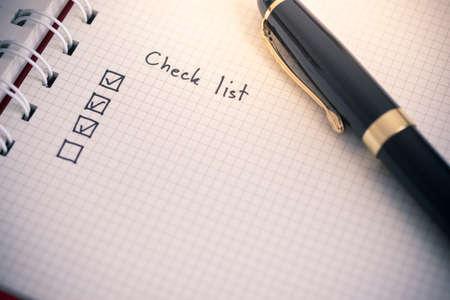 Lista de verificación escribiendo en papel de cuaderno de negocios