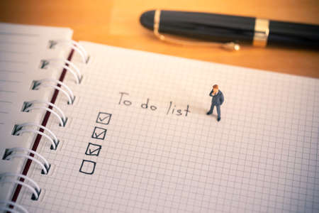 Businessman thinking with to do list on notebook paper