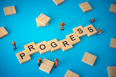 Business concept of progress. Workers arranging wood with text