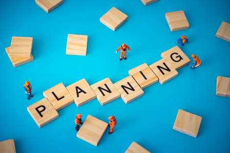 Business concept of planning. Workers arranging wood with text