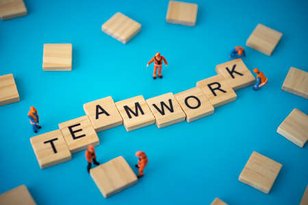 Business concept of teamwork. Workers arranging wood with text