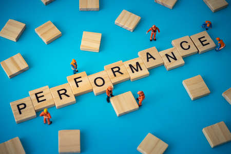 Business concept of performance. Workers arranging wood with text