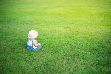 Adorable kid sit on green meadow grass field