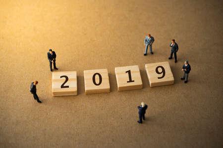 Businessmen standing around 2019 new year plan wood plate
