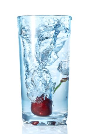cherry fell in a glass with water isolated on white  photo
