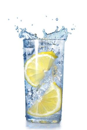 vaso con agua: dos limones cayeron en un vaso con agua aislado en blanco Foto de archivo