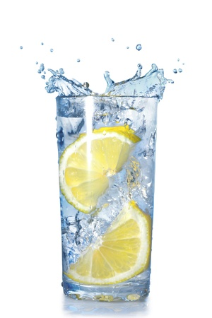 lemon water: two lemons fell in a glass with water isolated on white