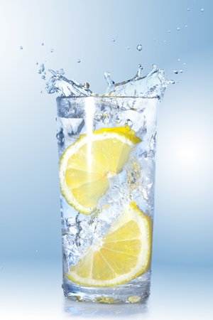 two lemons fell in a glass with water on gradient background