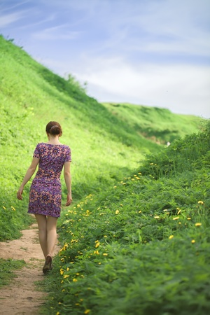 the girl goes on a footpath between hills covered with a fresh green grass. bright sunny day of summer. Stock Photo - 19865866