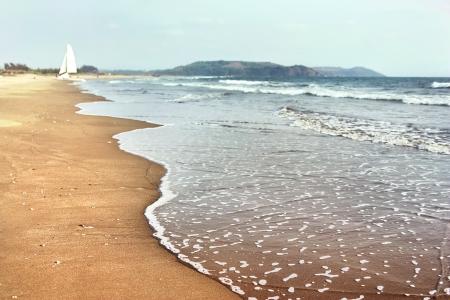 inflow: landscape: sandy beach, sea surf, blue sky, sailboat