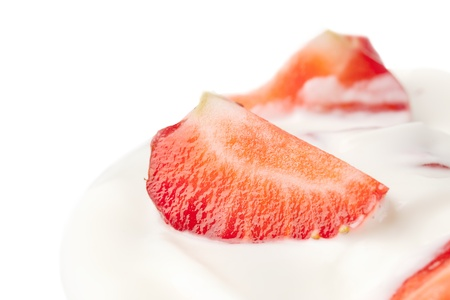 delicious fresh strawberry falling into glass with yogurt. over white photo