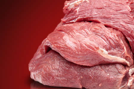 stake: raw beef stake on a red background