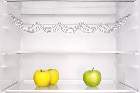 three apples in open empty refrigerator Фото со стока