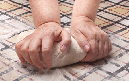 knead: grandmother hands knead the dough on the table