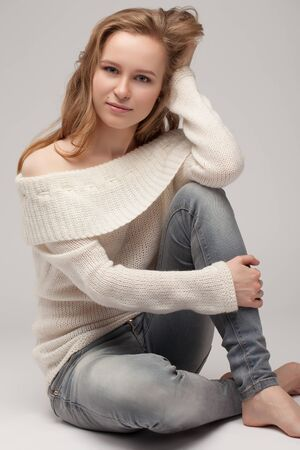 beautiful young girl posing and sitting on white background. blonde in a white sweater.