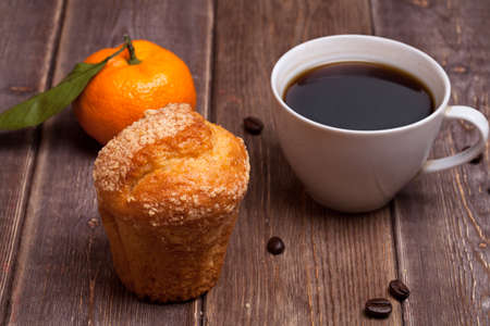tangerine cake and coffee cup on a wooden table. sweet breakfast.