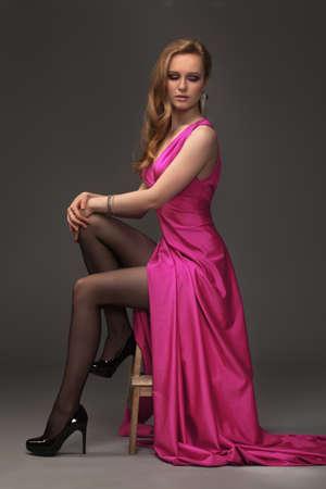 girl in evening dress posing over dark background