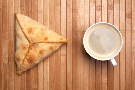 breakfast from coffee and pie-samsa on a wooden mat