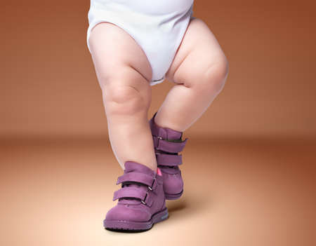 the stylish baby goes in boots. on a brown background