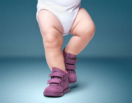 the stylish baby goes in boots. on a blue background
