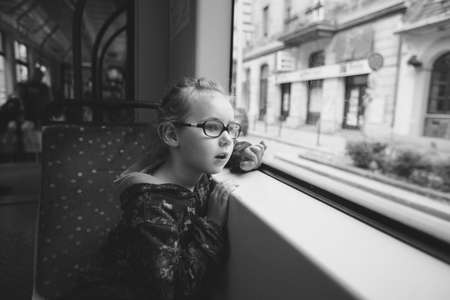 a young girl is riding in a tram and looks with curiosity on the sides