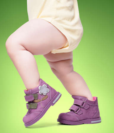 the stylish baby goes in boots. on a green backgroun