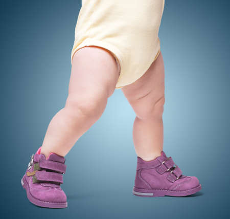 the stylish baby goes in boots. on color backgroun Foto de archivo