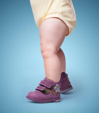 the stylish baby goes in boots. on color background