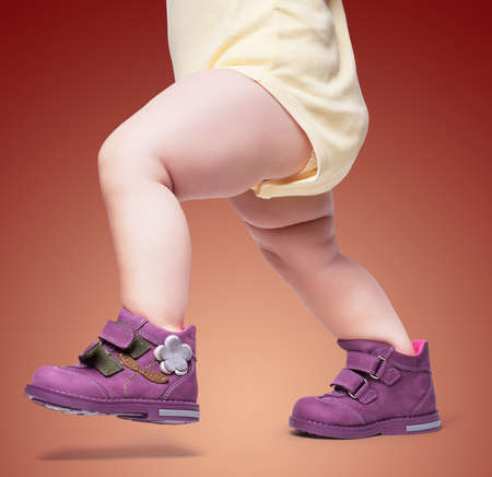 the stylish baby goes in boots. on a color backgroun Foto de archivo