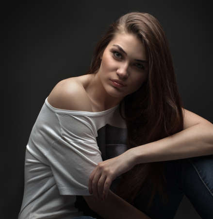 the beautiful girl poses in studio on a gray background. fashion portrait. make-up. long hair.