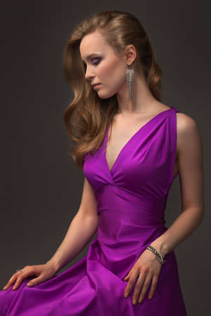 beautiful girl in evening dress posing over dark background