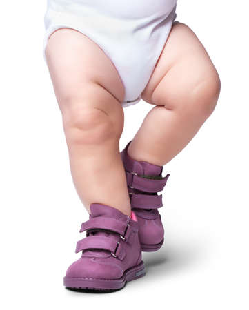 the stylish baby goes in boots. it is isolated on a white background Stock Photo