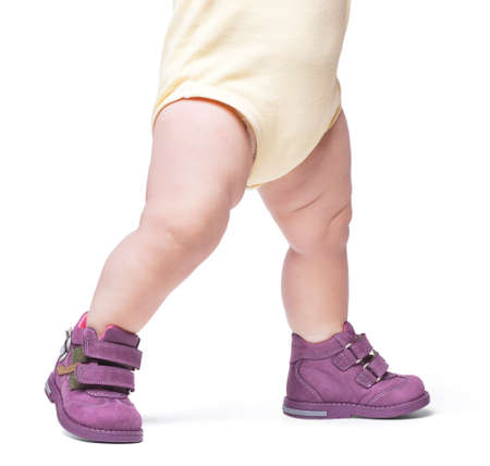the stylish baby goes in boots. it is isolated on a white backgroun