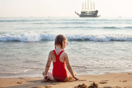 young beautiful girl in glasses and a red bathing suit sits on the beach