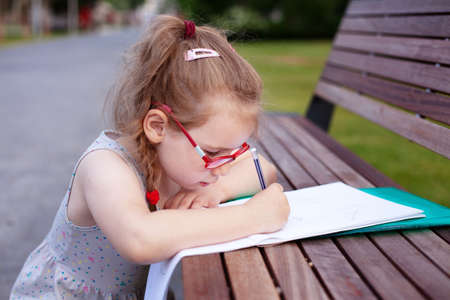 girl with glasses writes and draws in a notebook outdoors. homework in nature.